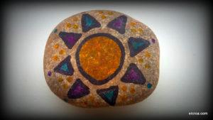 Sol pintado en piedra con rotuladores permanentes